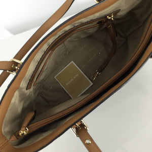 Michael Kors Tote - SHINE LIKE A STAR WITH THIS CLASSIC BROWN MK MONOGRAM TOTE! LIKE NEW CONDITION ON INSIDE AND OUT! HAS STAR CUT-OUTS ON BOTH SIDE POCKETS REVEALING GOLD UNDERNEATH. THE INSIDE HAS 9 SLOT POCKETS, 1 ZIPPER POCKET, AND 1 DIVIDING POCKET WITH ZIPPER CLOSURE.