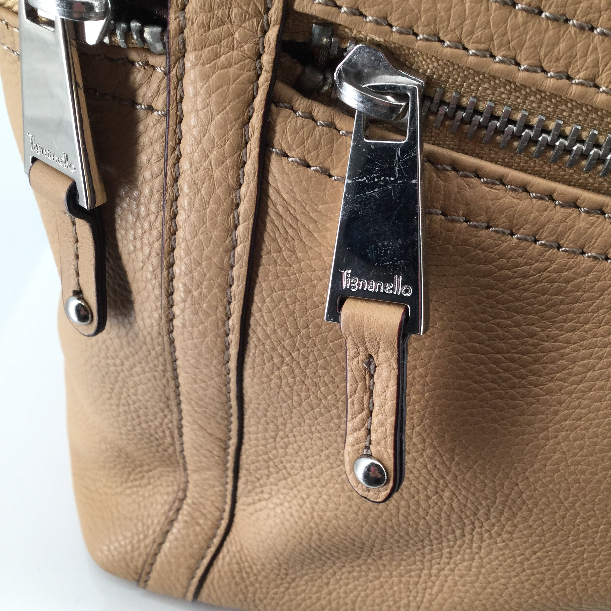 Tignanello  Purses Handbag Size:medium - NEW - TIGNANELLO PURSE STILL WITH TAGS ON IT.  GREAT ALL-PURPOSE CAMEL COLOR, USE ANY SEASON!  MULTIPLE EXTERIOR POCKETS,  SILVER HARDWARE. TWO LARGE INTERIOR COMPARTMENTS, WITH CENTER ZIPPER AREA.  SIDE POCKETS TOO.