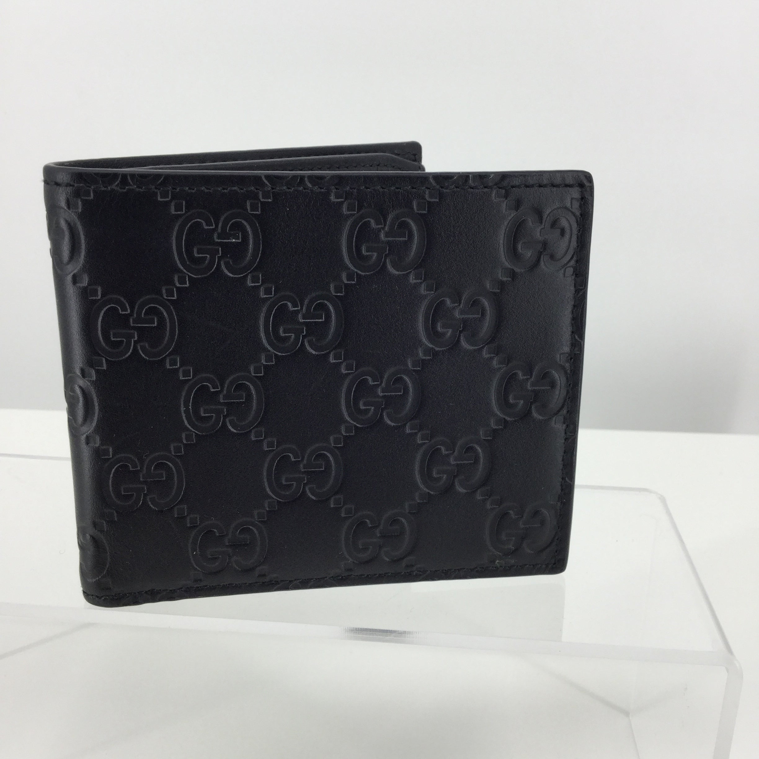 ACCESSORIES,PURSES AND HANDBAGS - BUFFED LEATHER BIFOLD WALLET IN BLACK. LOGO PATTERN EMBOSSED THROUGHOUT. EMBOSSED LOGO, CARD SLOTS, AND NOTE SLOTS AT INTERIOR. TONAL TEXTILE LINING. TONAL STITCHING. APPROX. 4.5