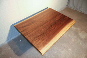 image of a live edge walnut top shows lighter coloured sap wood on the edges and darker walnut colouring in the centre