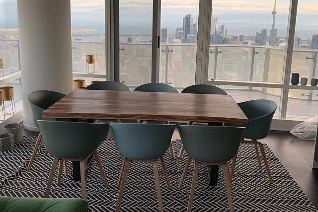 small condo size live edge table in an apartment looking out at the CN Tower in Toronto
