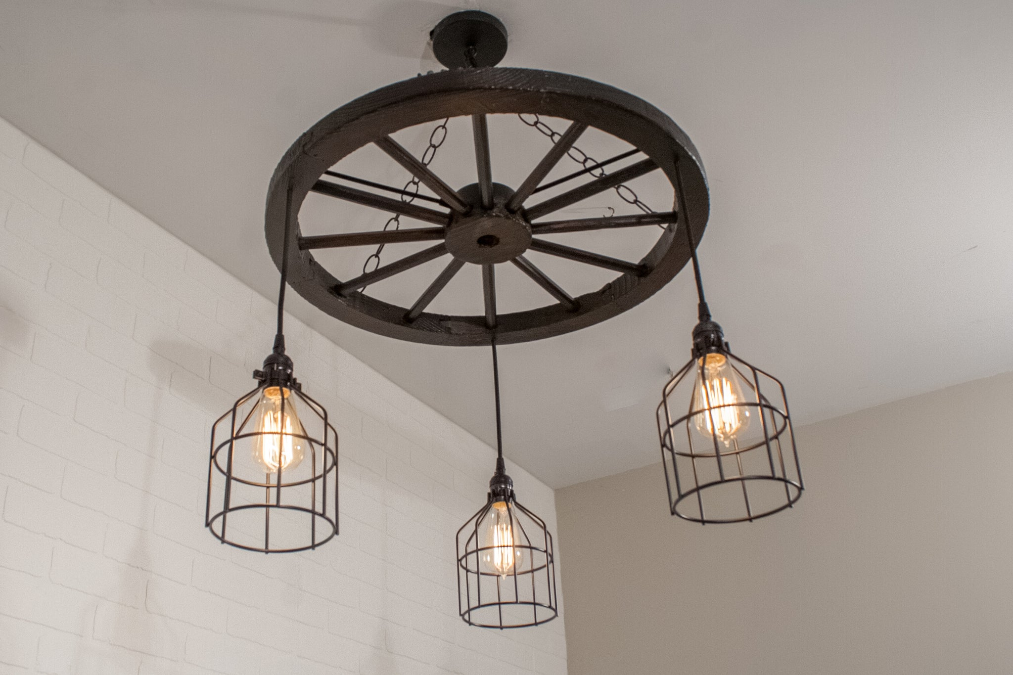 rustic light fixture featuring wagon wheel light with cages