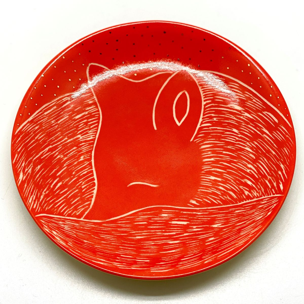 A small flame orange plate with a small fox
