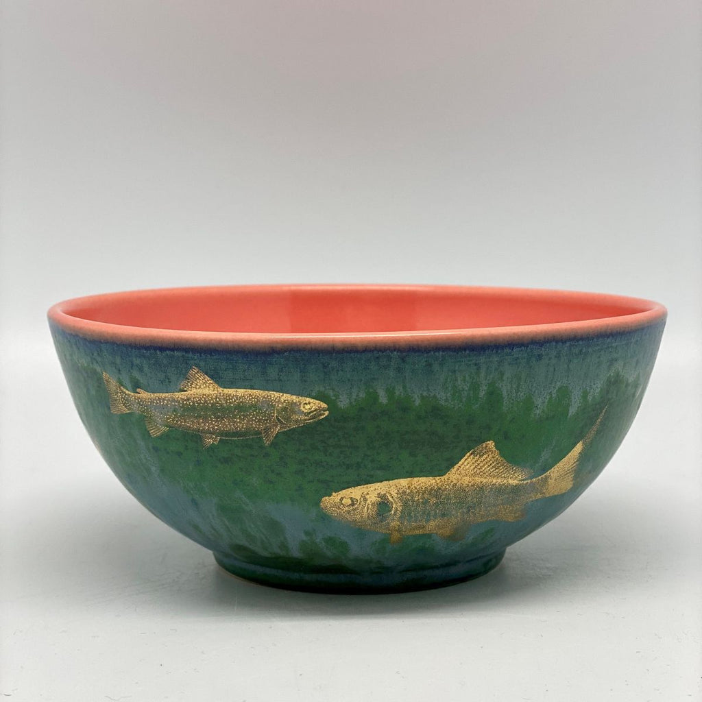 A small green-blue bowl with golden fish