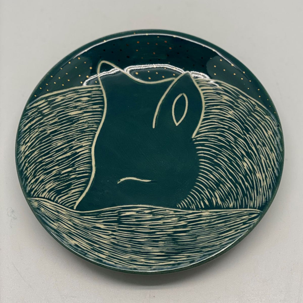A small green plate with a small fox