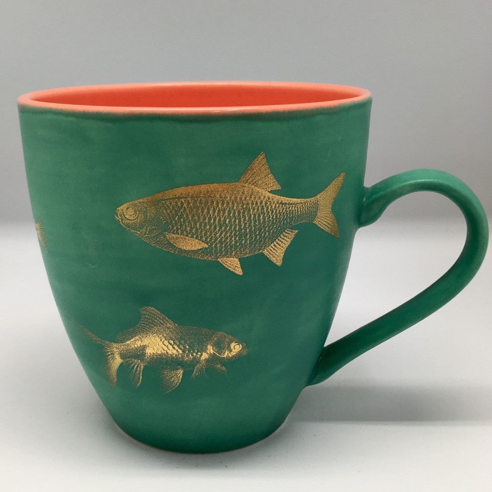A huge emerald green mug with golden fish