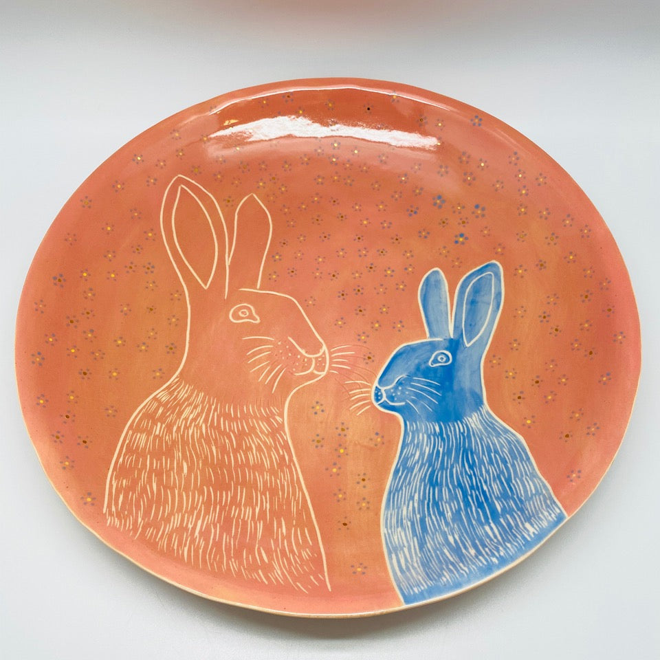 A platter with a small and big rabbit and forget-me-nots.