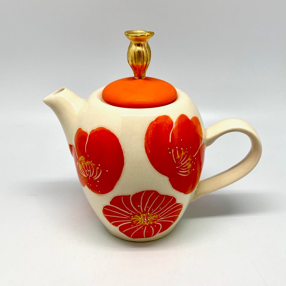 A small teapot with poppies