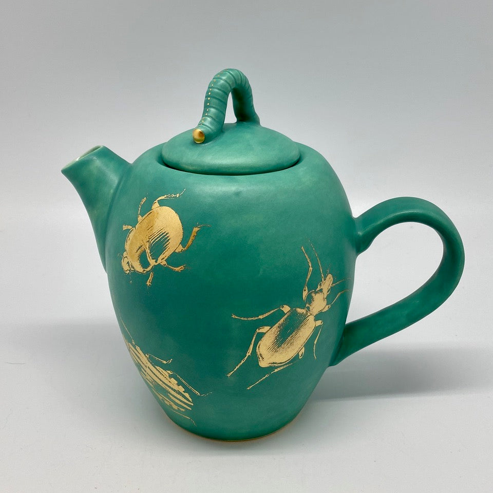 A small emerald green teapot with bugs