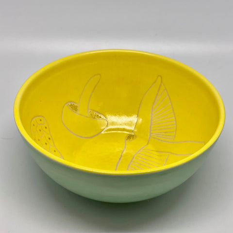 A small bright yellow bowl with mushrooms