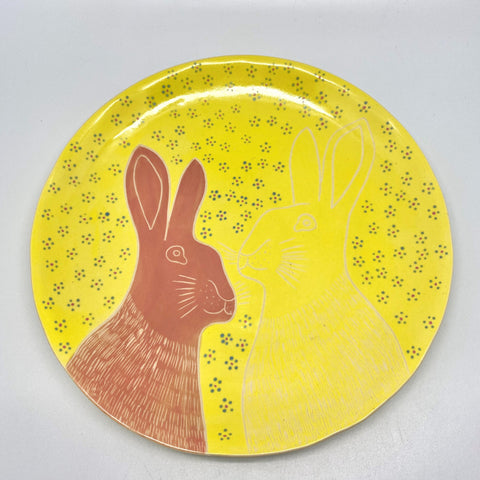 A bright yellow plate with bunnies