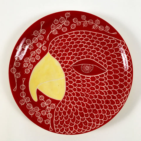 A plate with a bird and red currants