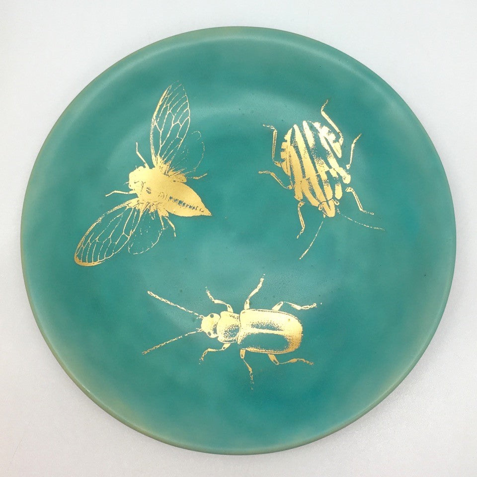 A small plate with golden bugs