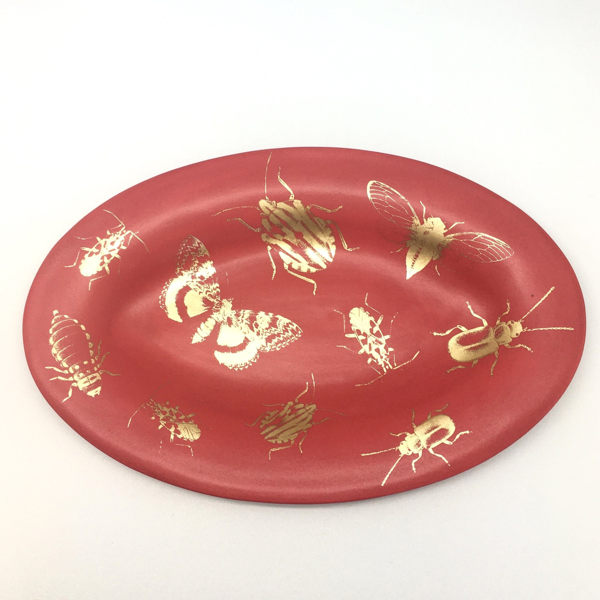 Red matte oval plate with golden bugs