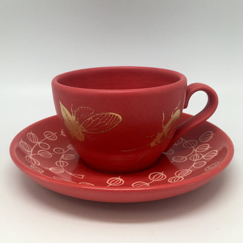 Red teacup with golden bugs and a saucer with currants