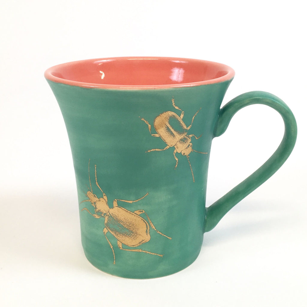 Green mug with golden bugs