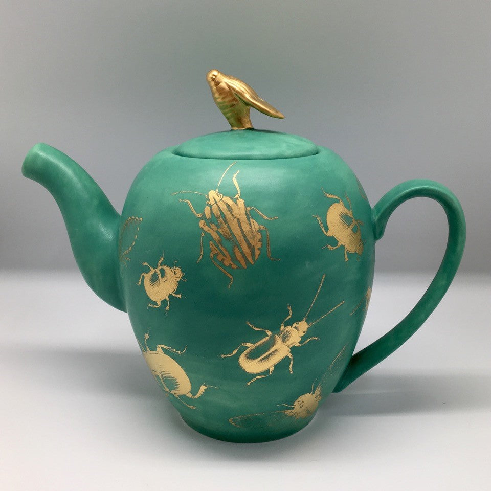 A big emerald green teapot with golden bugs