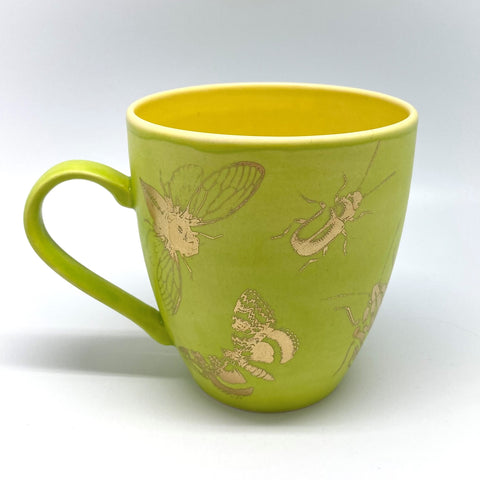 A big salad green mug with golden bugs