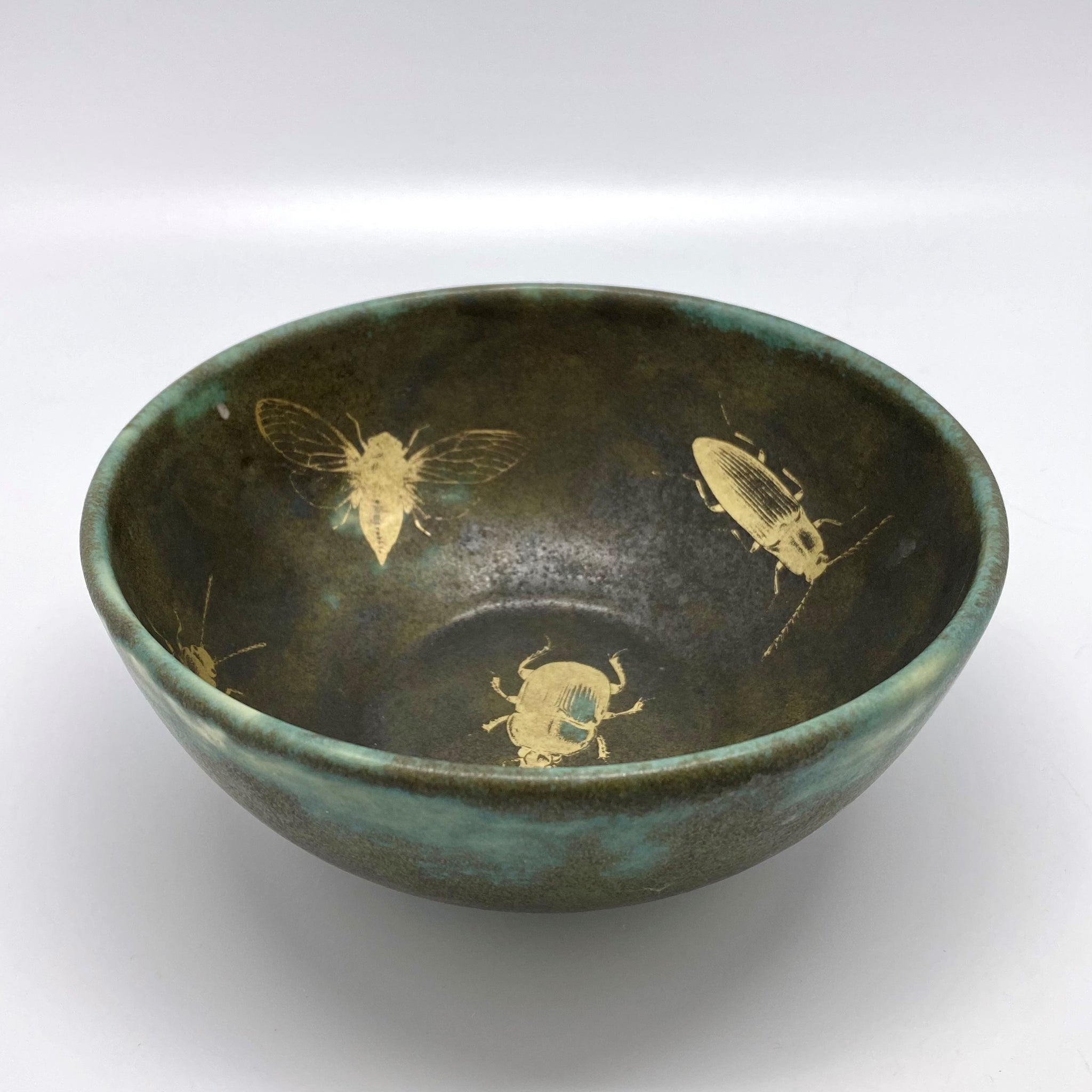 A small moss green bowl with golden bugs