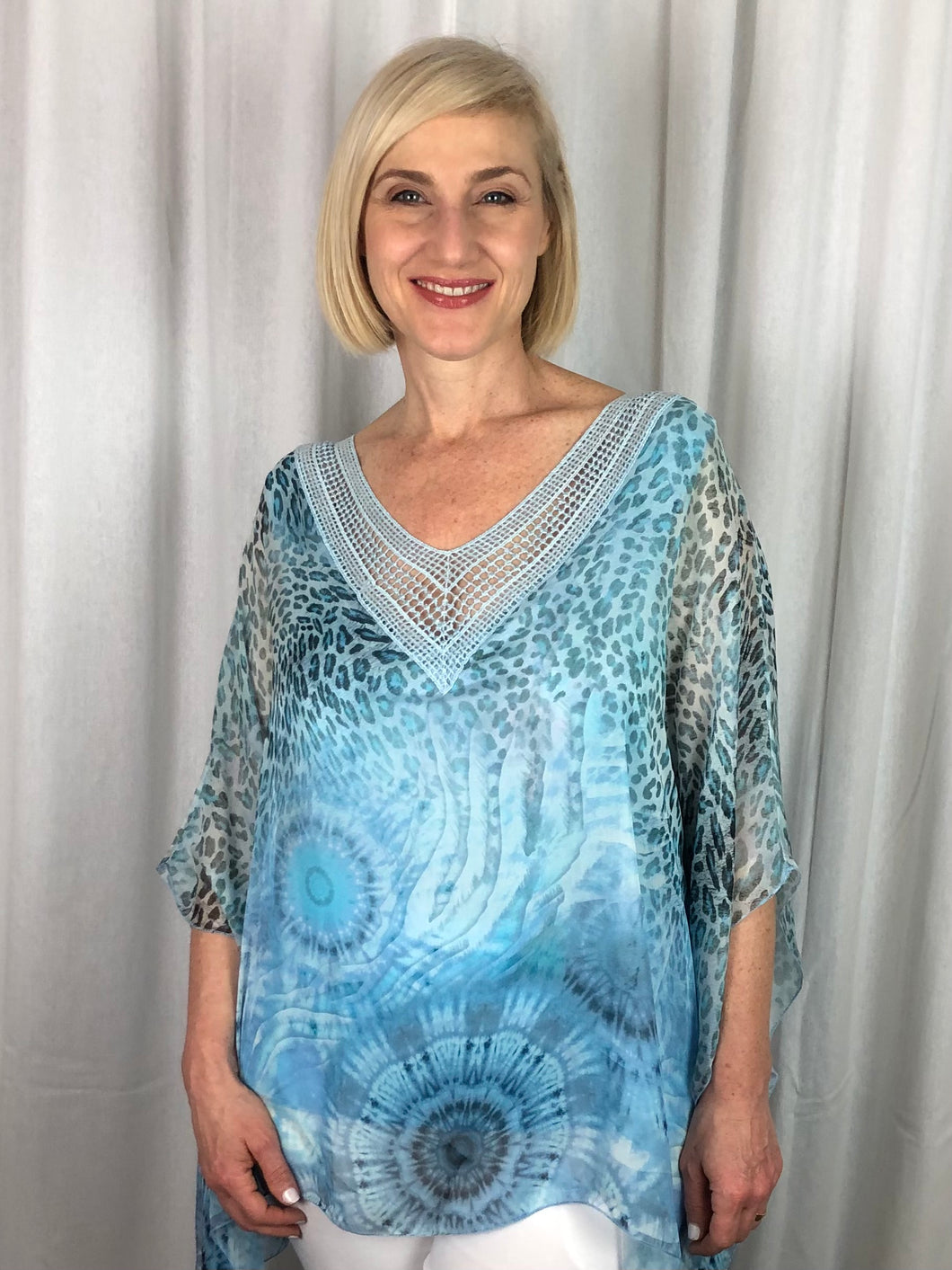 Looking for that special piece this Summer, look no further than our Celeste Flutter Top in soft tones of turquoise. Made in Italy from a blend of Silk, Viscose and Elastane this gorgeous top with camisole sewn underneath features a feminine sequinned and crocheted V-Neck.
