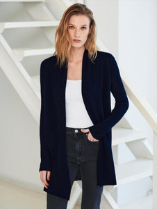 Woman standing with one hand in front pant pocket. Wearing a deep navy cardigan, a white top, and dark blue jeans.