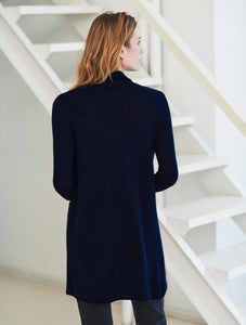 Back view of a woman standing. Wearing a deep navy cardigan and dark blue jeans.