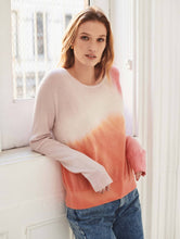 Load image into Gallery viewer, Woman standing in a bright room with wide windows behind her, wearing a pink and orange tie-dye cashmere long sleeve sweater.