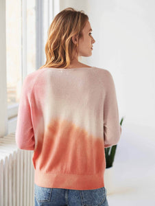 Back view of woman standing in a bright room with wide windows behind her, wearing a pink and orange tie-dye cashmere long sleeve sweater.