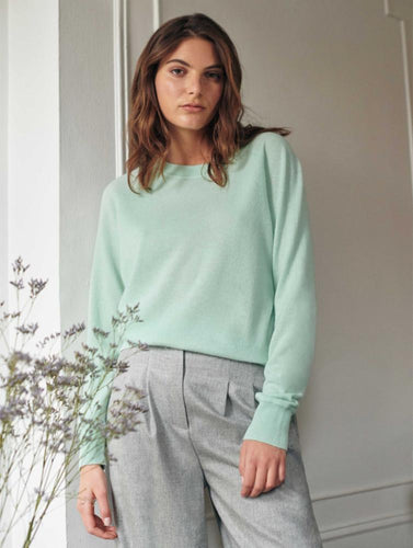 Woman standing against a white wall and next to a lavender plant on the left side. Wearing a mint colored cashmere long sleeve sweater and grey trousers.