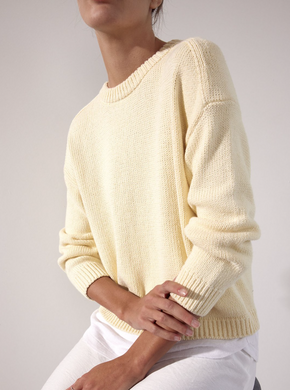 Photo of a woman from the neck down sitting on a stool wearing a pale yellow crew neck sweater with a white linen fabric layered underneath.