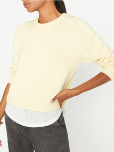 Photo of a woman from the neck down standing with one hand on her hip, wearing a pale yellow crew neck sweater with a white linen fabric layered underneath.