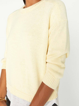 Load image into Gallery viewer, Close up of a woman wearing a pale yellow crew neck sweater with a white linen fabric layered underneath.