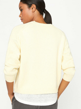 Load image into Gallery viewer, Back view of a woman looking to the side, wearing a pale yellow crew neck sweater with a white linen fabric layered underneath.