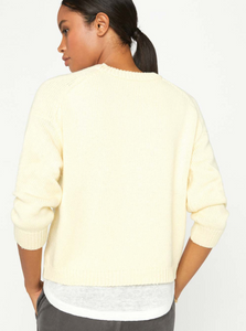 Back view of a woman looking to the side, wearing a pale yellow crew neck sweater with a white linen fabric layered underneath.