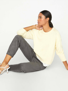 Woman sitting on the floor with one knew bent upward, wearing a pale yellow crew neck sweater with a white linen fabric layered underneath.