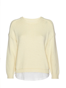 Still image of a pale yellow crew neck sweater with a white linen fabric layered underneath.