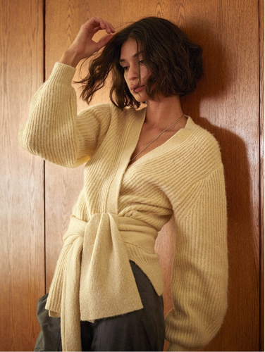 Woman leaning on wooden wall, wearing a yellow, ribbed cashmere cardigan with matching chunky belt attached.