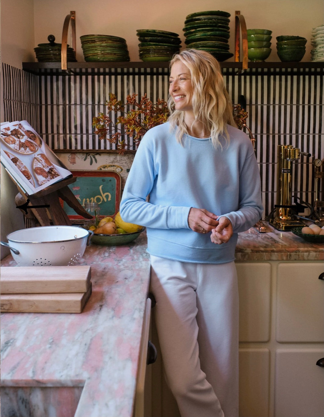Woman standing in kitchen smiling and looking out a window. Wearing white sweatpants and a light blue long sleeve sweater.