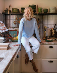 Woman smiling and sitting on the counter in a kitchen. Wearing white sweatpants, brown sandals, and a light blue long sleeve sweater.