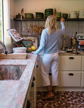 Load image into Gallery viewer, Back view of a woman standing in a kitchen, reaching for a bowl on a high shelf. Wearing white sweatpants, brown sandals, and a light blue long sleeve sweater.