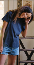 Load image into Gallery viewer, Woman standing and laughing. Wearing a navy blue short sleeve t-shirt and jean shorts.