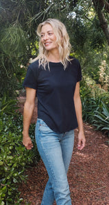 Woman standing outside surrounded by plants and trees. Wearing a navy blue short sleeve t-shirt and blue jeans.