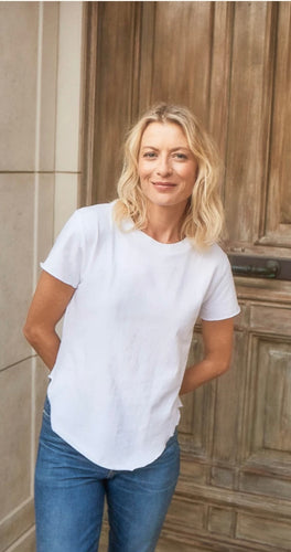 Woman standing in front of door with her arms behind her back. Wearing a white short sleeve t-shirt and blue jeans.