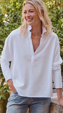 Woman smiling and standing with one hand in front pocket of blue jeans. Wearing a white loose fitting top with a v-neck and collar standing up.