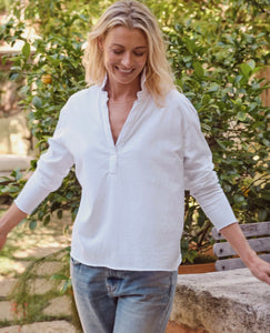 Woman smiling while standing up. Her arms are slightly lifted to her sides. Wearing blue jeans and white, long sleeve, loose fitting top with v-neck and collar standing up.