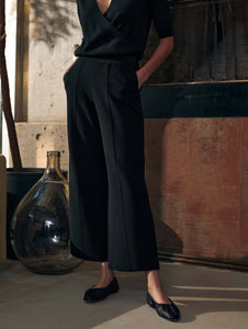 Close up of a woman standing  by a fireplace, wearing an all black outfit. Black  slim cut pants that flare out at the bottom. Cropped at the ankle.