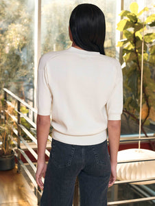 Back view of woman standing in a contemporary room filled with plants. She is wearing a cream colored wrap top with mid-length sleeves.