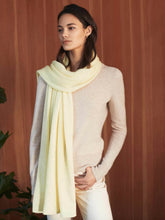 Load image into Gallery viewer, Woman standing with one hand in pocket. Wearing a pale yellow wrap wound her neck.