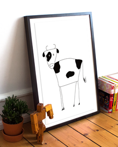 Framed black and white illustration of a cow on the floor with a plant and books