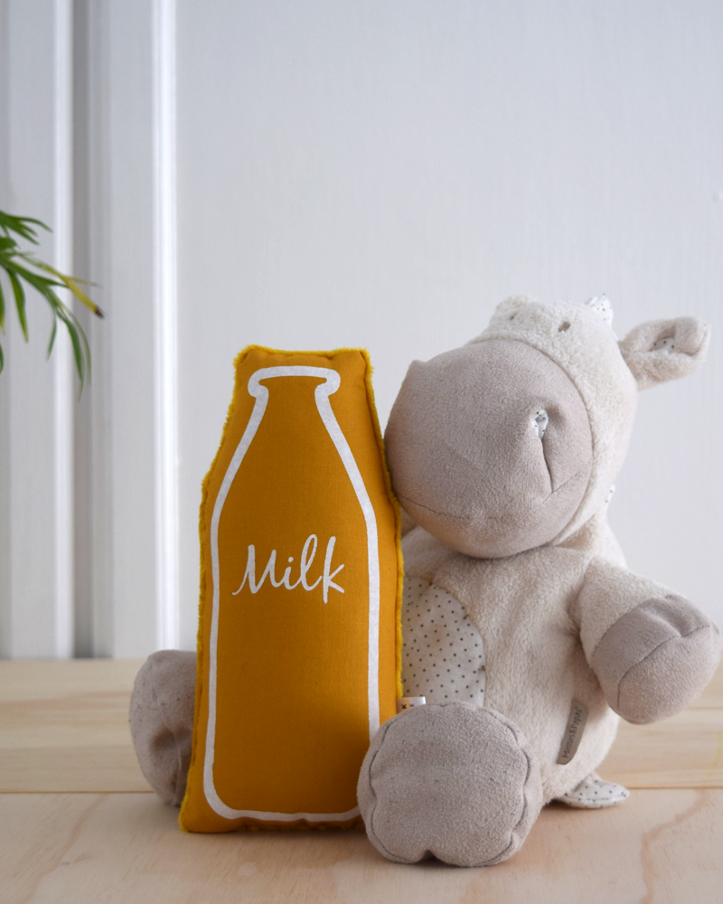 mustard coloured milk bottle rattle for babies. screen printed by hand in white ink. Shown with a white soft toy hippo